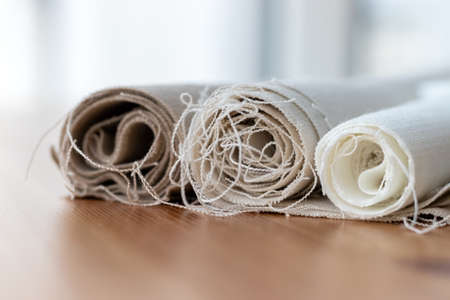 Three rolls of natural linen fabric in different colors with protruding threads on a wooden table. Selective focus. Closeup view. Blurred background