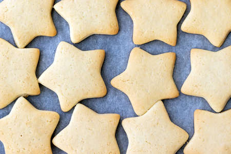 Baked shortbread cookies in the form of stars on a baking sheet with parchment paper just taken out of the oven. Tea snack for breakfast. Selective focus. Closeup view Stock fotó