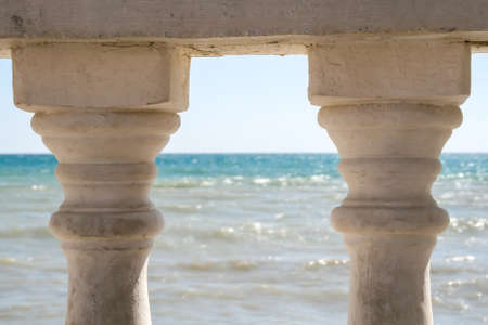 View of the rippling sea through two old pillars of the fence