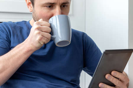 A man in a blue t-shirt holds the gray cup with one hand, drinking from it, and holds the electronic book with the other hand. Reading an e-book or news on a tablet at breakfast. Selective focus