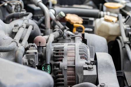 Alternator. Dusty details of a flat-four (boxer) car engine compartment under the open hood. Closeup side view Reklamní fotografie
