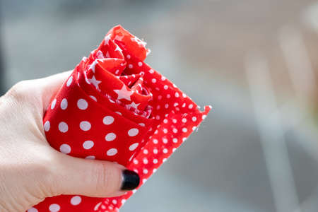 Female hand holds a roll of red and white fabrics against a blurred background. Selective focus. Closeup view Banque d'images