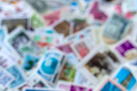 Blurred defocused background texture from multicolored postage stamp collection
