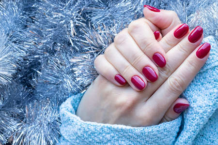 Female hands in a blue knitted sweater with a beautiful glossy manicure - burgundy, dark red, cherry color nails on background of silver Christmas tinsel garland with copy space