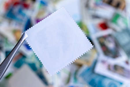 Blank square postage stamp against blurred background collection of multicolored postage stamps of different countries. Selective focus
