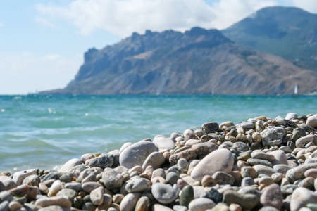 Sea coast with pebbles against the blurred mountains and the sea
