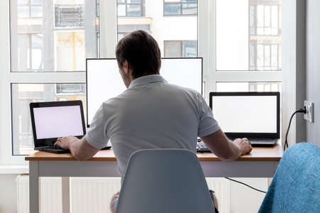 A man in a white t-shirt is sitting at a workplace with two laptops and a monitor near the window. Remote work from home in quarantine. Back view