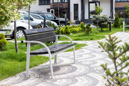 Wooden and metal bench in a beautiful green courtyard with many plants in a gated community. A place for a relaxing break from the bustle of the city near the apartment building