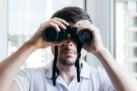 Handsome man looking through binoculars at the camera near the window with a view of the neighboring house for observing environment or nature during quarantine. Selective focus. Closeup view
