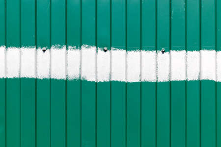 Green metal fence with vertical corrugated stripes, with a horizontal stripe of white paint in the middle and with three bolts Reklamní fotografie