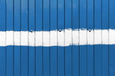 Classic blue metal fence with vertical corrugated stripes, with a horizontal stripe of white paint in the middle and with three bolts Reklamní fotografie