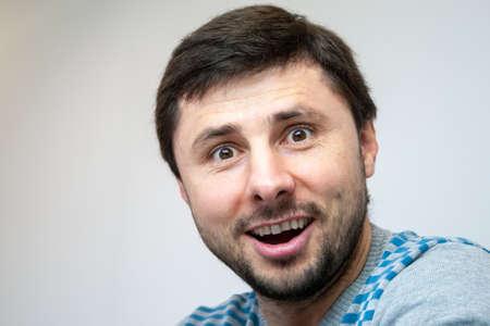 Overjoyed smiling handsome bearded man looks surprised in camera Stock fotó