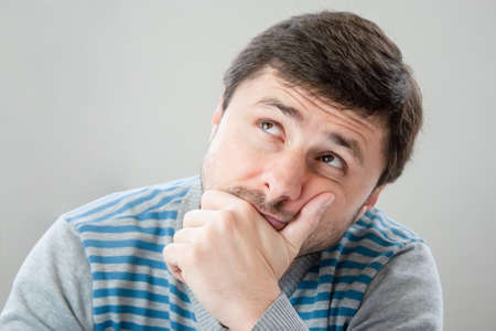 Thoughtful handsome bearded man in a striped sweater leaning his head against his hand looking up