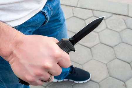 A man in blue jeans and a white t-shirt with a black pocket out the front knife in his hand