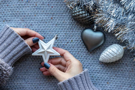 Female hands in knitted sweater with white star with beautiful manicure - dark gray blue glittered nails on knitted background with silver tinsel garland and Christmas tree toys: heart and pine cones 写真素材