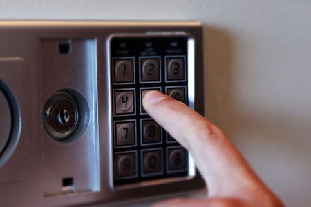 Blurred safe with combination lock and human hand in a hotel room, closeup numbers with tilt shift effect. Selective focus