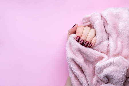 Female hand with beautiful manicure - dark red glittered nails with fluffy fabric, textile on pink background with copy space