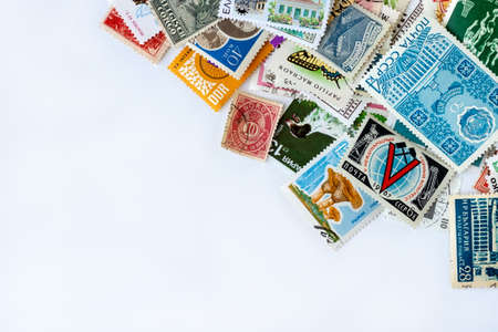Corner border made of multicolored postage stamps collection from different countries on white background