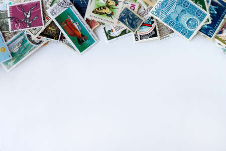 Top border made of multicolored postage stamps collection from different countries on white background