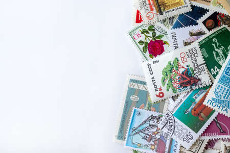 Multicolored postage stamps collection from different countries on white background Stock fotó