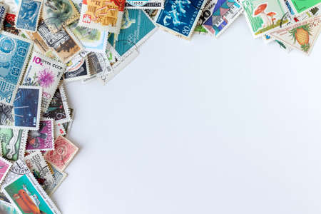 Corner frame border made of multicolored postage stamps collection from different countries on white background Stock fotó