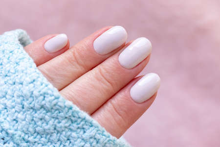 Female hand in blue knitted sweater with beautiful manicure - white ivory nails on blurred pale pink background