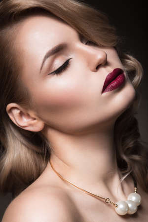 makeup artists: Beautiful blonde in a Hollywood manner with curls red lips. Beauty face. Picture taken in the studio Stock Photo