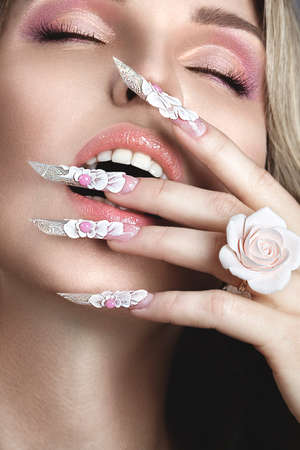 Beautiful blonde girl with long nails perfect skin and a ring in the form of a flower. Picture taken in the studio. Stok Fotoğraf