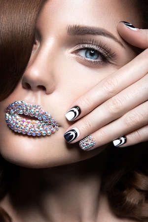 Beautiful girl with bright nails and lips of crystals long eyelashes and curls. Beauty face. Stockfoto
