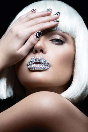 Elegant beautiful girl in a white wig with the lips of rhinestones and festive manicure. Beauty face. photo