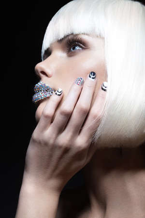Elegant beautiful girl in a white wig with the lips of rhinestones and festive manicure. Beauty face.