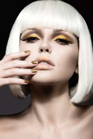 Beautiful girl in a white wig with gold makeup and nails. Celebratory image. Beauty face photo