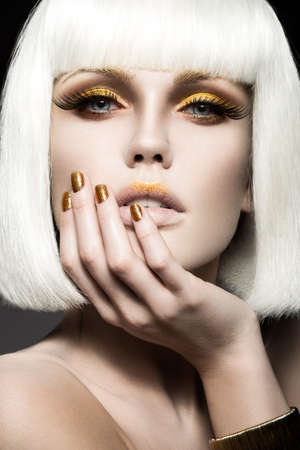 Beautiful girl in a white wig with gold makeup and nails. Celebratory image. Beauty face Stok Fotoğraf