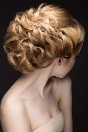 hair dress: Portrait of a beautiful blond woman in the image of the bride. Picture taken in the studio on a black background. Beauty face. Hairstyle back view