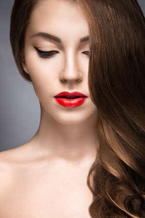poses de modelos: Mujer hermosa con maquillaje de la tarde los labios rojos y rizos. Cara de la belleza. Fotograf�a tomada en el estudio sobre un fondo gris.