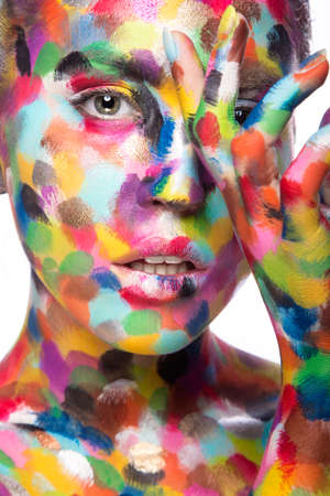 Girl with colored face painted. Art beauty image. Picture taken in the studio on a white background.