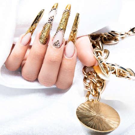 Schöne lange Nägel in eine gold Design mit Strasssteinen. Nagelkunst. Standard-Bild - 41387353