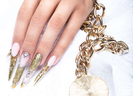 Beautiful long nails in a gold design with rhinestones. Nail art. Stock Photo