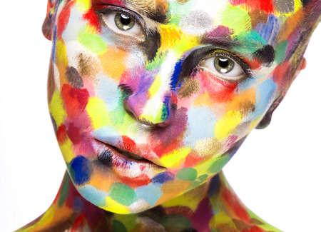 Muchacha con la cara pintada de color. Imagen Belleza Arte. Fotografía tomada en el estudio sobre un fondo blanco.