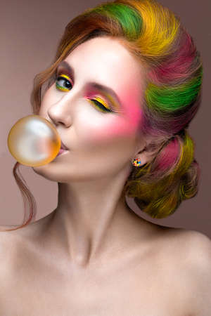 colorful paint: Fashion Girl with colored face and hair painted. Art beauty image. Picture taken in the studio on a pink background.