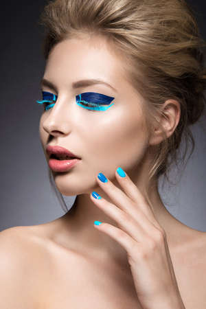 makeup: Beautiful girl with bright creative fashion makeup and blue nail polish. Art beauty nail design. Picture taken in the studio.