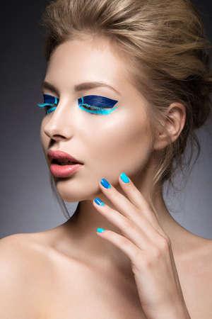 maquillage: Belle fille avec maquillage lumineux de façon créative et bleu vernis à ongles. Art conception beauté des ongles. Photo prise dans le studio. Banque d'images