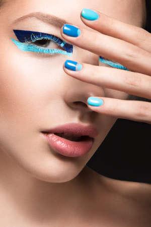 明るく創造的なファッション メイクや青いマニキュアで美しい少女。アート美容ネイル デザインです。スタジオでの撮影。