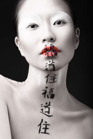Beautiful Asian girl with white skin, red lips and hieroglyphics on her face. Art Beauty image. Picture taken in the studio on a black background.