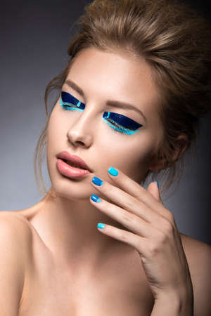 nail studio: Beautiful girl with bright creative fashion makeup and blue nail polish. Art beauty nail design. Picture taken in the studio.