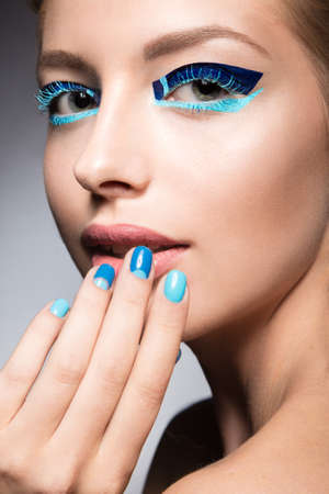 hair studio: Beautiful girl with bright creative fashion makeup and blue nail polish. Art beauty nail design. Picture taken in the studio.