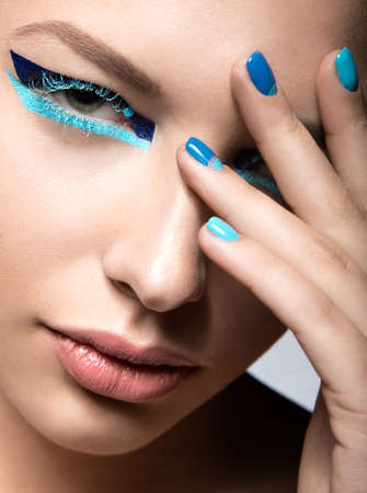 Beautiful girl with bright creative fashion makeup and blue nail polish. Art beauty nail design. Picture taken in the studio.