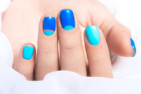 and of blue: Blue manicure in light and dark colors of lacquer on a white background. Nail art design