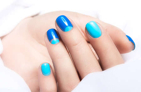 nail lacquer: Blue manicure in light and dark colors of lacquer on a white background. Nail art design