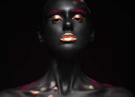ファッションの色メイクアップと浅黒い肌の少女の肖像画。美容顔。黒の背景にスタジオでの撮影。 写真素材